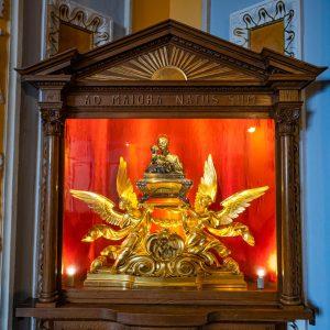 Złota rzeźba umieszczona w drewnianej podświetlonej gablotce