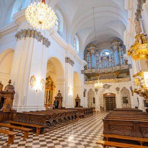 Wnetrze barokowej światyni, dwa rzędy drewnianych ławek, bogato zdobiona i złocona ambona