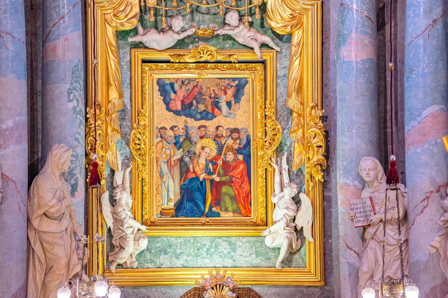 Kolorowy obraz podwójnej złotej ramie. Po obu bokach obrazu kamienne rzeźby