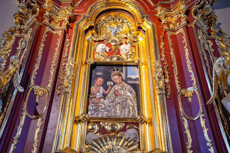 Obraz matki boskiej z dzieciątkiem. Matka boska w bogatych szatach i koroną. Obraz umieszczony jest w ołtarzu