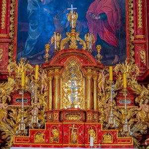 Fragmentbarokowego ołtarza.. Dominuje złoto i czerwień. W środku zlote tabernakulum