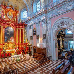 Wnętrze barokowoego koscioła. zdobiony ołtarz czerwono-złoty z dużym obrazem w środku. Posadzka z brązowo-białych płytek