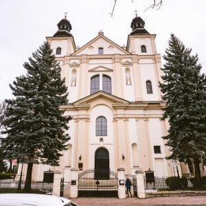 Dwuwieżowy zabytkowy kościół koloru kremowego/ Przed kościołem drzewa iglaste