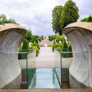 Most ze szkła, po bokach betonowe konstrukcje tworzące wejście do ogrodu
