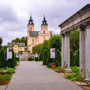 Portyk z czterema klasycznymi kolumnami ustawiony w ogrodzie w dali tablice i barokowy kościół z dwoma wieżami