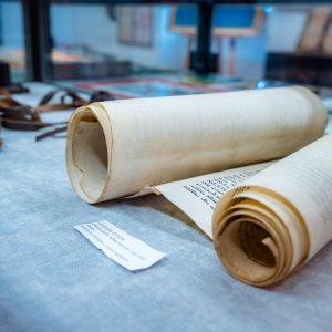 Rulon paieru z napisami po hebrajsku leży na błekitnym suknie