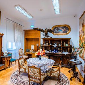 Salon z zabytkowymi meblami. Po środku okrągły stół nakryty białą serwetą