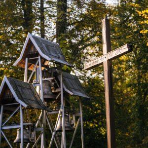 Drewniana dzwonnica z trzema dzwonami, obok drewniany krzyż