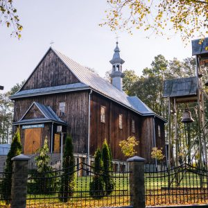Drewniany zabytkowy kościół, obok dzwonnica