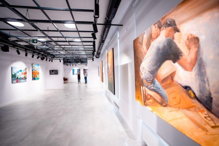 Wnętrze sali wystawowej z rozwieszonymi kolorowymi obrazami