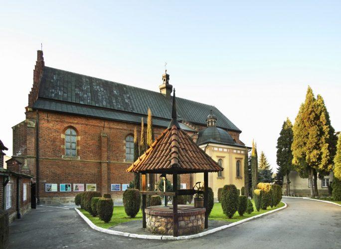 Kościół z czerownej cegły, bez wieży. Na pierwszym planie studnia przykryta daszkiem krytym dachówkami