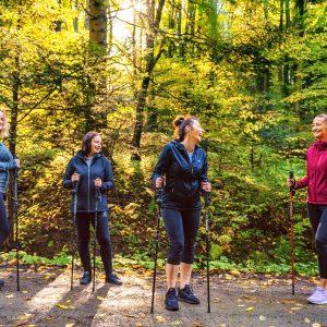 Cztery uśmiechnięte kobiety z kijkami do Nordic walking stoją na leśnej drodze.