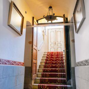Schody nakryte czerwonym dywanem. Na piwrwszym planie korytarz z dwoma obrazami
