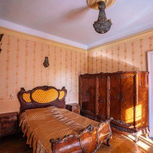 Zabytkowa sypialnia z duzym łożem i drewnianą szafą. Na suficie wisiu żyrandol