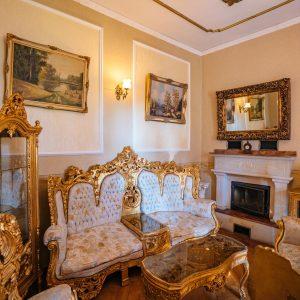 Salon z barokowymi złoconymi meblami wyściełanymi białym materiałem  - kanapa i fotel na ścianach obrazy. W głebi kominek