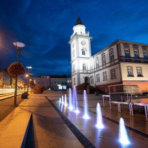 Zabytkowy budynek z wieżą nakrytą szpiczastym hełmem. Budynek iluminwany, przed nim podświetlane fontanny