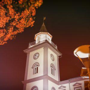 Podświetlona wieża ze szpiczastym hełmem i zegarem