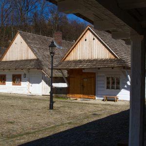Chaty z bali, pomalowanych na biało, ze spadzistymi dachami. Na pierwszym planie drewniane podcienia