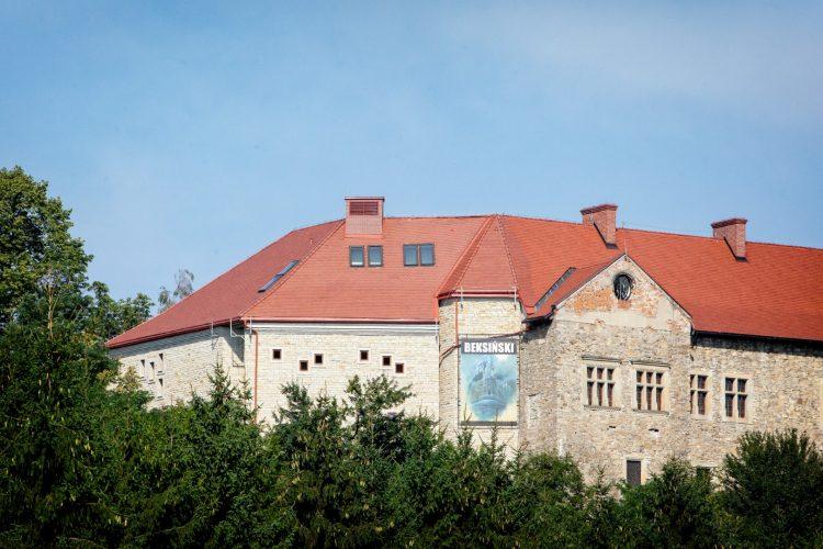 Zabytkowa budowla z szarego kamienia z czerwonym spadzistym dachem