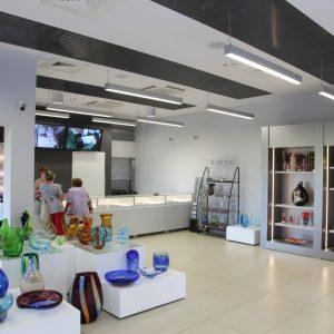 Nowoczesne wnętrze wystawowe z postumentami i witrunami, w których poukładane są naczynie z kolorowego szkła