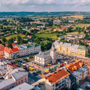Widok z lotu ptaka na rynek z ratuszem z wieżą otoczony kamienicami. Na drugim planie niskie wzgórza