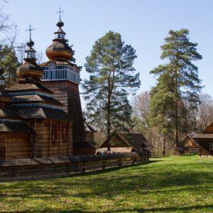 Drewniana cerkiewka z trzena wieżami różnej wielkości otoczona drewnianym ogrodzeniem, Z tyłu drewnaina chata ze spadzistym dachem