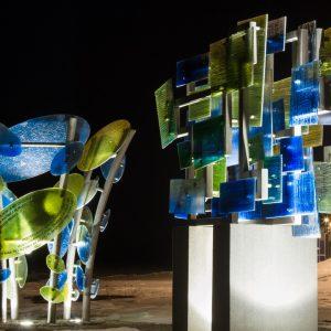 Dwa podświetlone dzieła sztuki wykonane z zielonych i niebieskich kawałków szkła. Dzieła umieszczone sa na zewnątrz